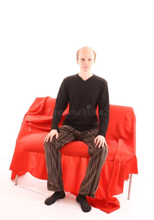 Homem novo que senta-se no sofá vermelho isolado imagem de stock