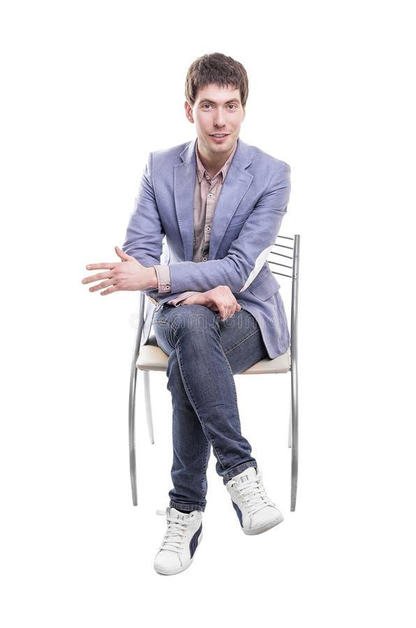 Homem novo que senta-se no tamborete fotografia de stock