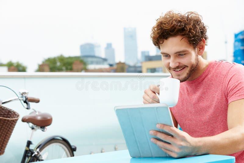 Homem novo que senta-se no terraço do telhado usando a tabuleta de Digitas fotos de stock royalty free