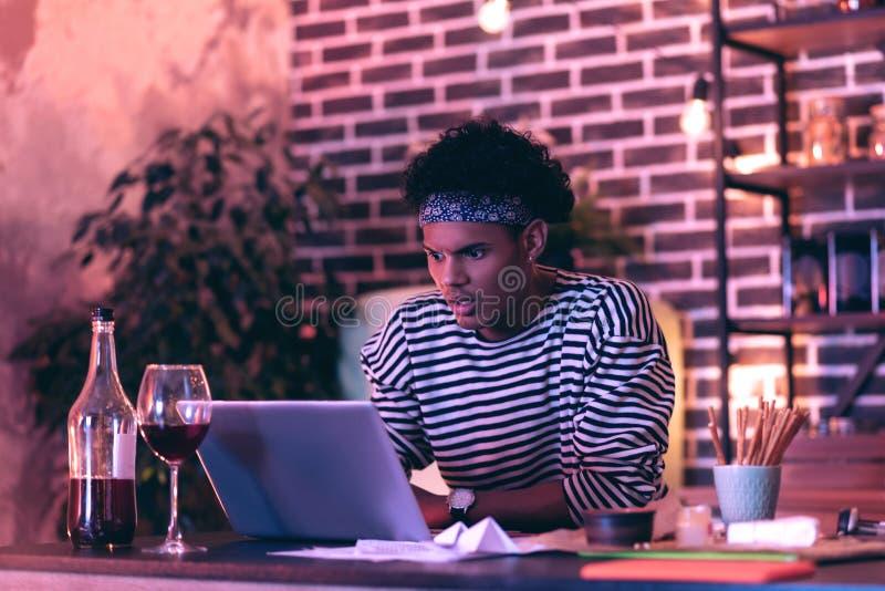 Homem novo que senta-se perto dos lápis e de uma garrafa do vinho e que tenta encontrar o documento no desktop do computador fotos de stock