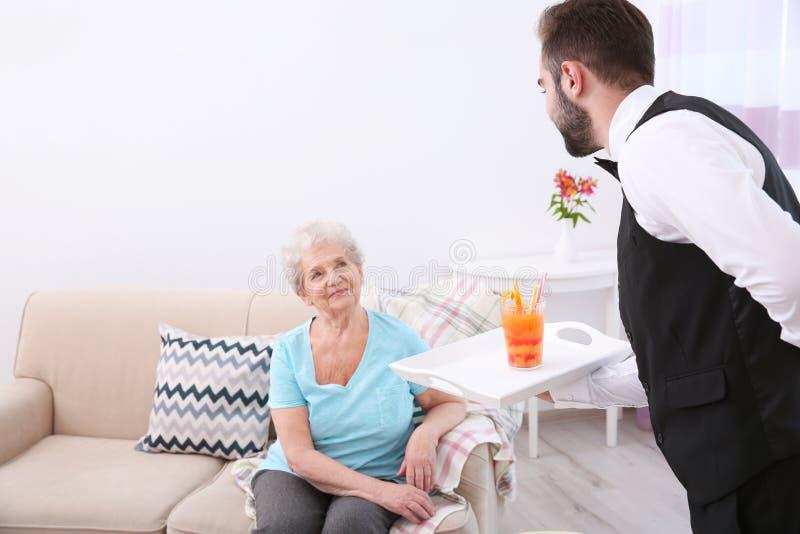 Homem novo que serve o vidro do suco para a mulher idosa foto de stock royalty free