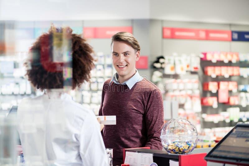 Homem novo que sorri ao comprar um produto farmacêutico útil imagem de stock royalty free