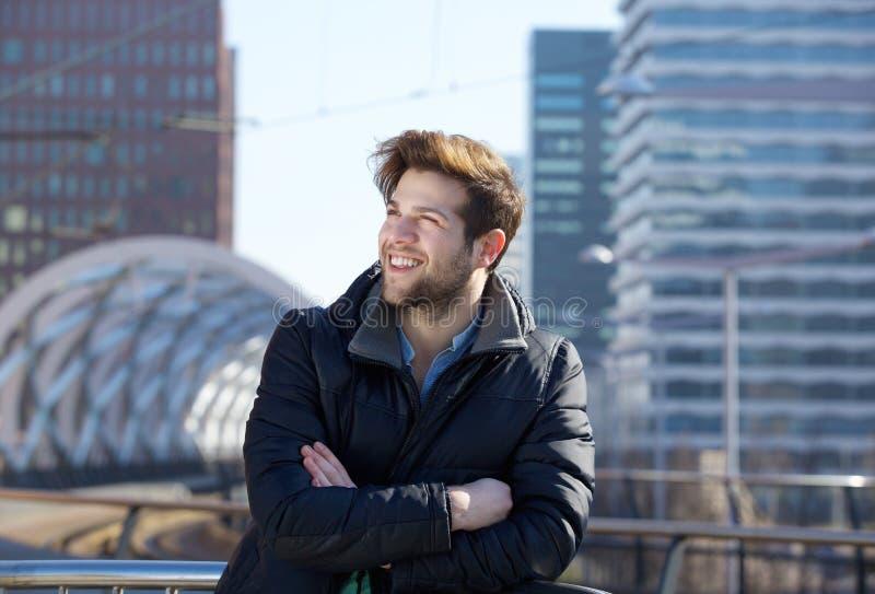 Homem novo que sorri com o revestimento do inverno na cidade imagens de stock royalty free
