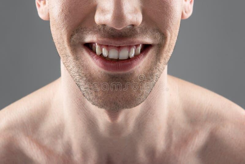 Homem novo que sorri e que demonstra seus dentes saudáveis brancos fotografia de stock