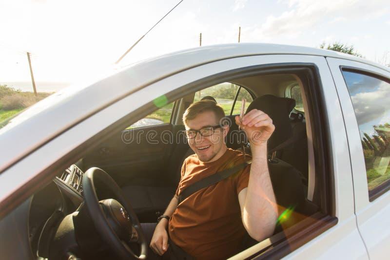 Homem novo que sorri e que guarda chave em seu carro Auto conceito da compra e dos povos fotografia de stock royalty free