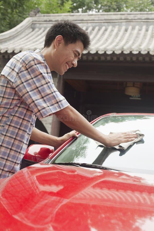 Homem novo que sorri e que limpa seu carro fotos de stock royalty free