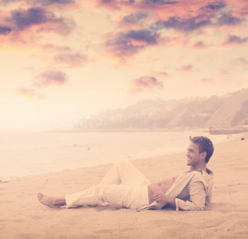 Homem novo que sorri na praia imagens de stock