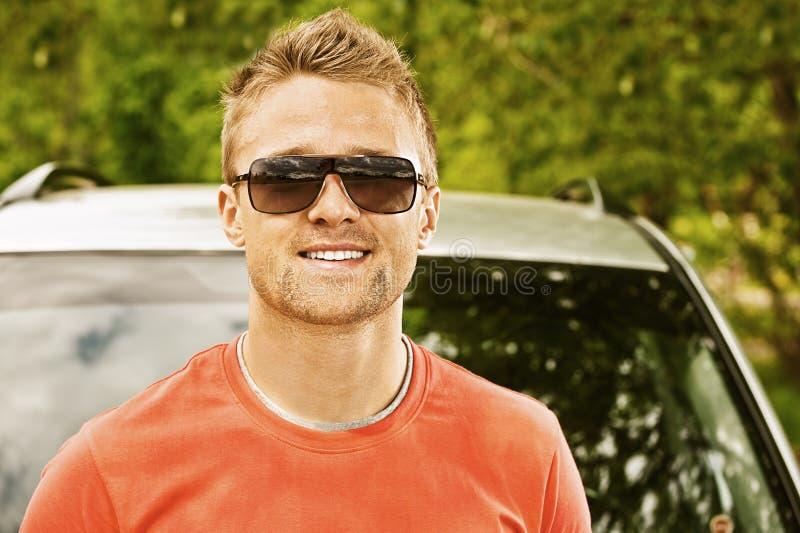Homem novo que sorri sobre o carro foto de stock royalty free