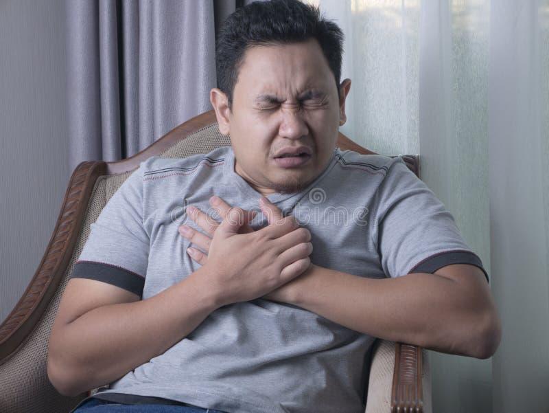 Homem novo que tem a dor no peito foto de stock
