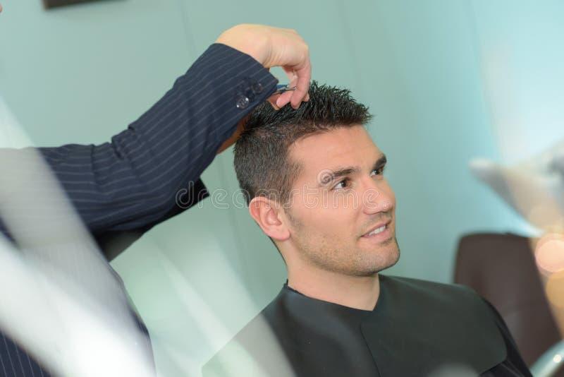 Homem novo que tem o corte de cabelo com tesouras imagem de stock royalty free