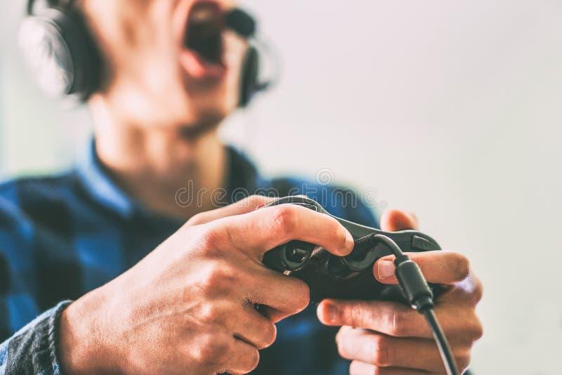 Homem novo que tem o divertimento que joga os jogos de v?deo que usam em linha os fones de ouvido e o microfone - fim acima do ga fotografia de stock royalty free