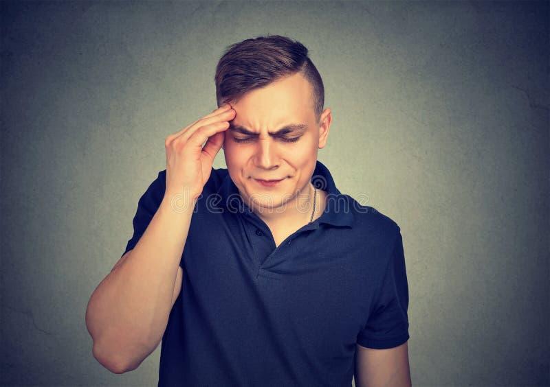 Homem novo que tem uma dor de cabeça imagem de stock royalty free