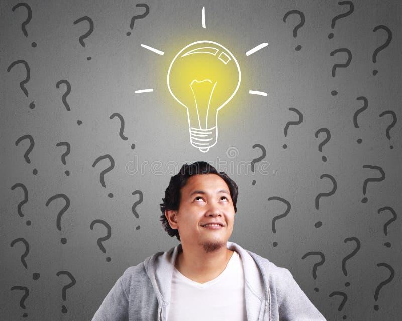 Homem novo que tem uma ideia com a ampola acima de sua cabeça imagens de stock royalty free