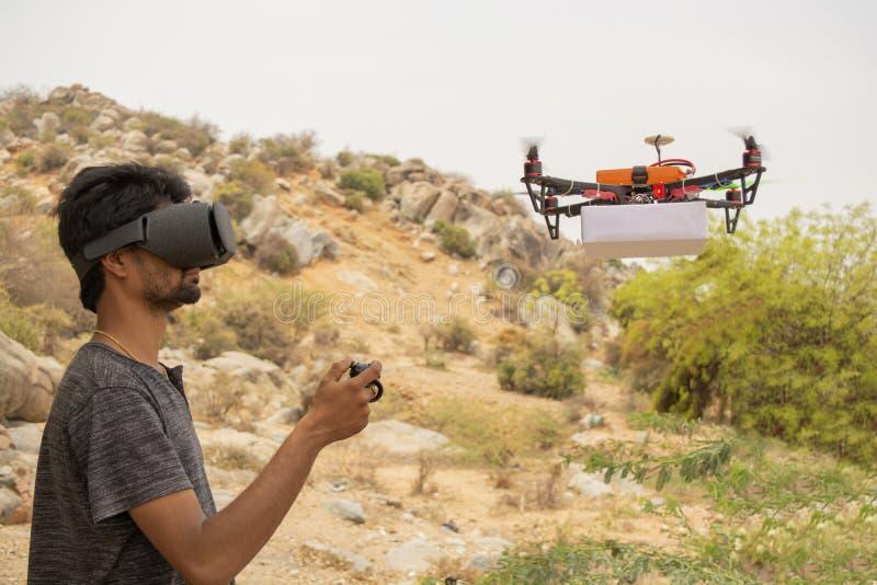 Homem novo que tenta controlar o zangão pelo controlador vendo no visor da realidade virtual foto de stock