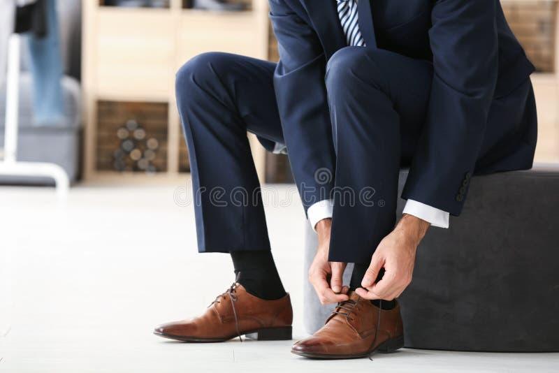 Homem novo que tenta em sapatas foto de stock royalty free