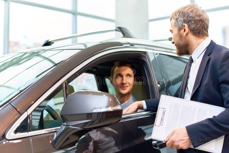 Homem novo que testa o carro novo na sala de exposições foto de stock