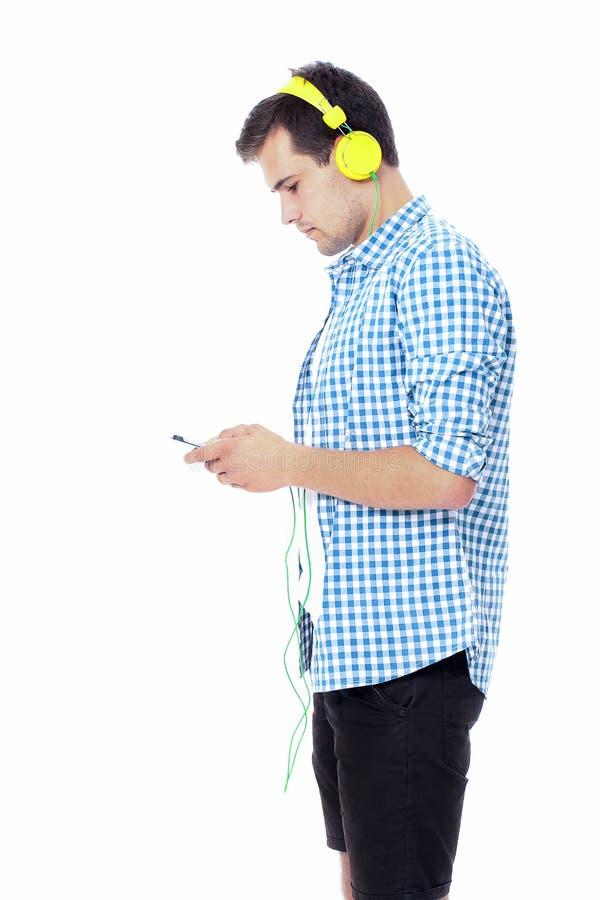 Homem novo que texting em seu telefone e que escuta a música Isolado no fundo branco Copie o espaço Zombaria acima Conversa do es fotos de stock royalty free