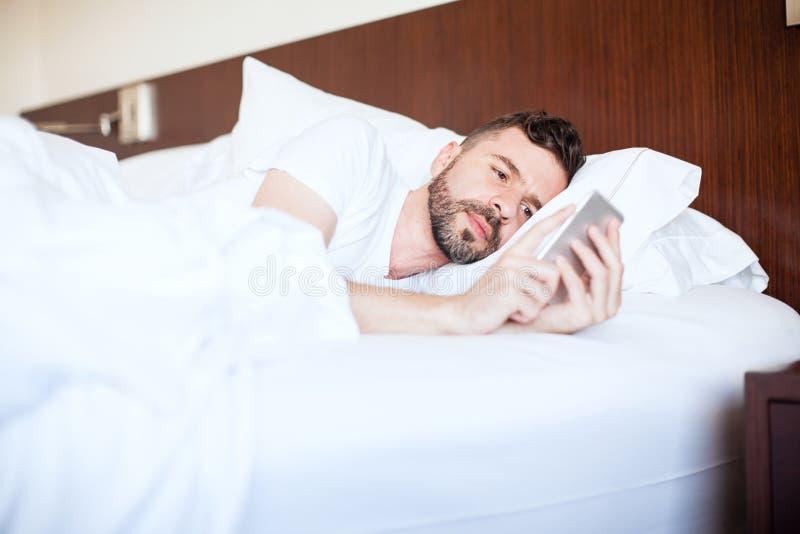 Homem novo que texting na cama imagens de stock