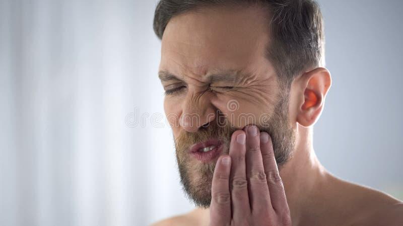 Homem novo que toca em seu mordente, sofrendo da dor de dente terrível, sensibilidade imagem de stock