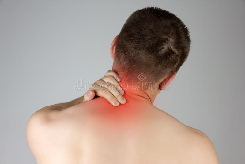 Homem novo que toca em seu pescoço para a dor fotografia de stock