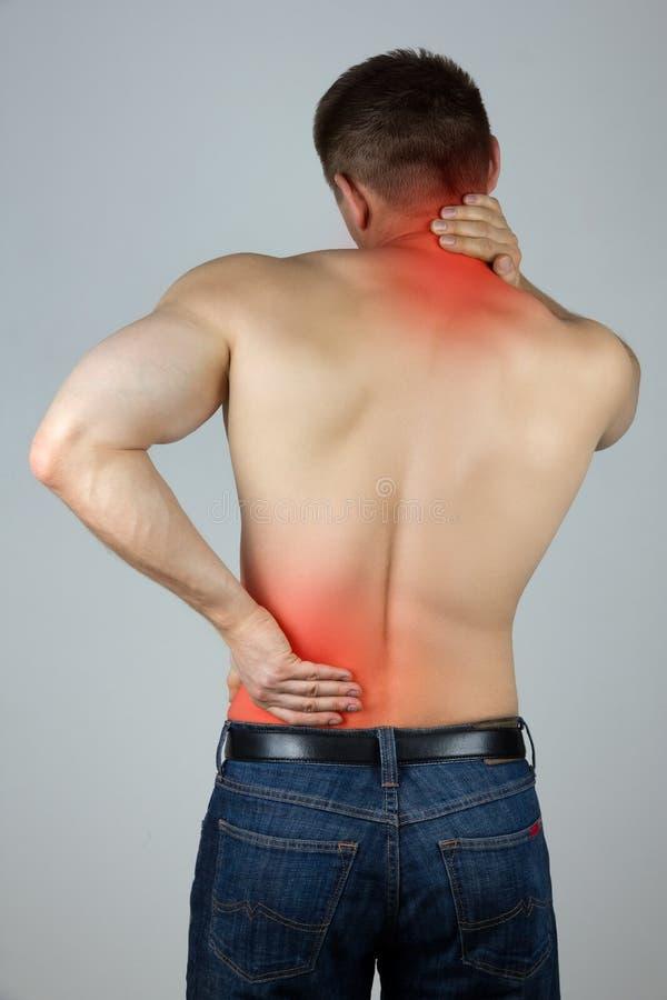 Homem novo que toca em seus parte traseira e pescoço para a dor imagem de stock