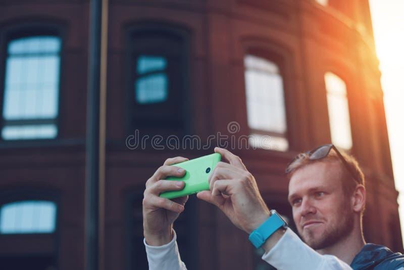 Homem novo que toma a foto com o smartphone na rua fotografia de stock