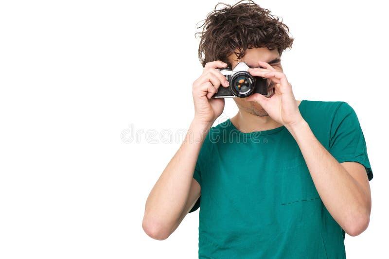 Homem novo que toma a imagem com câmera fotografia de stock