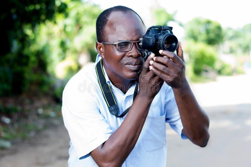 Homem novo que toma imagens com uma câmara digital na campanha imagens de stock