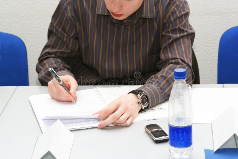 Homem novo que toma notas na sala de reuniões fotografia de stock royalty free