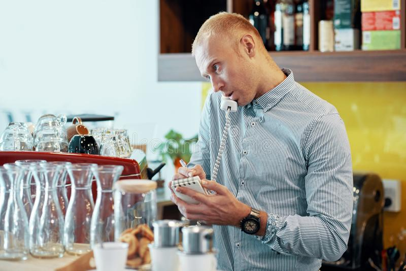 Homem novo que toma a ordem de telefone no bar fotografia de stock royalty free