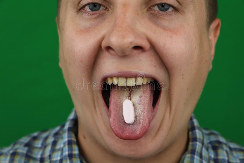 Homem novo que toma um comprimido foto de stock royalty free