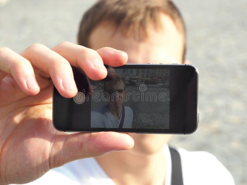 Homem novo que toma um Selfie com seu telefone celular foto de stock royalty free