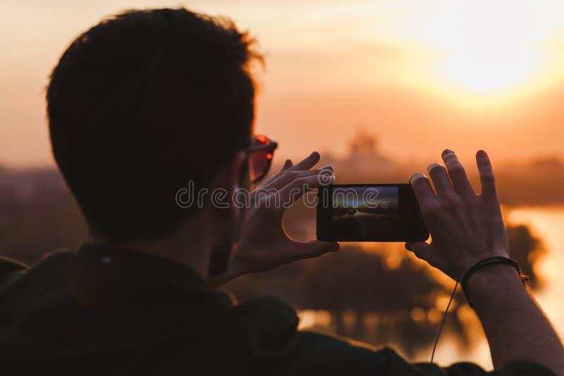 Homem novo que toma uma imagem do sunse imagens de stock