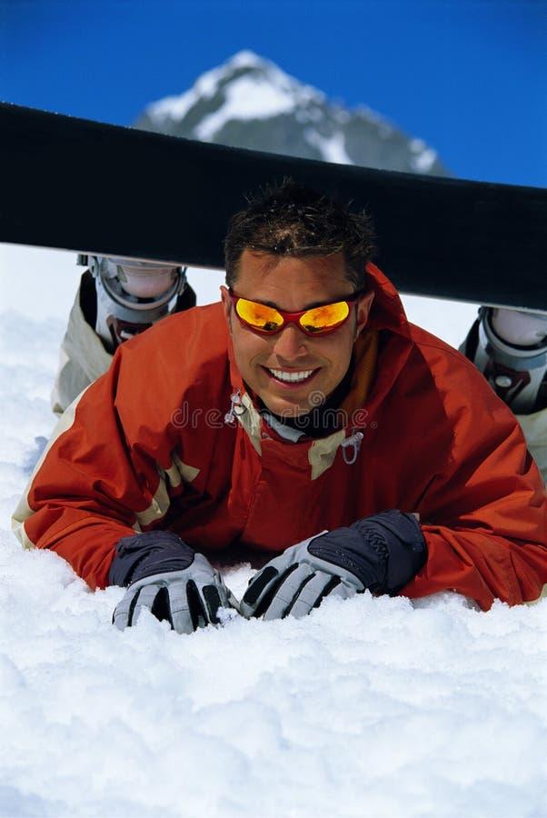 Homem novo que toma uma ruptura da snowboarding foto de stock