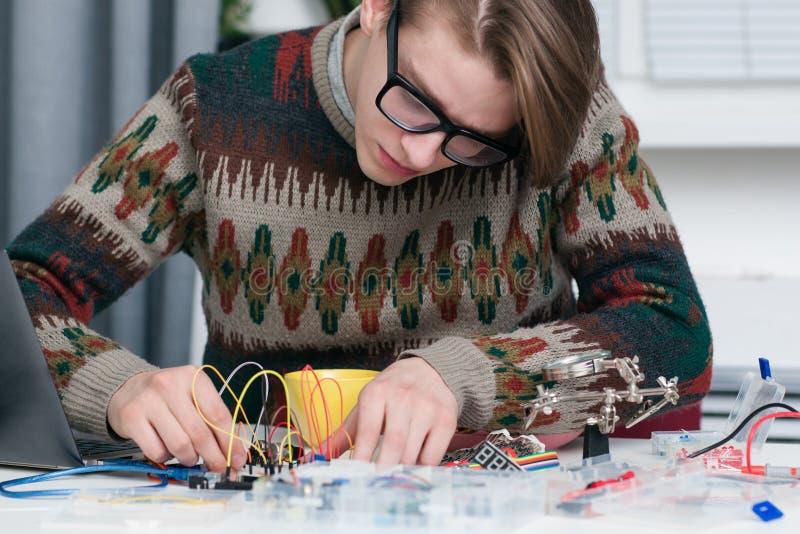 Homem novo que trabalha atentamente com peças eletrônicas foto de stock royalty free