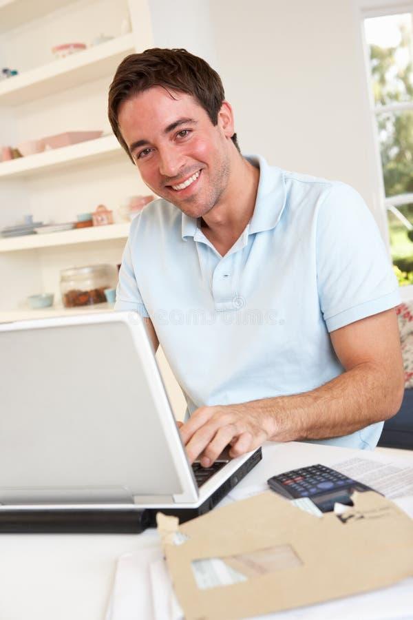 Homem novo que trabalha com computador portátil fotografia de stock