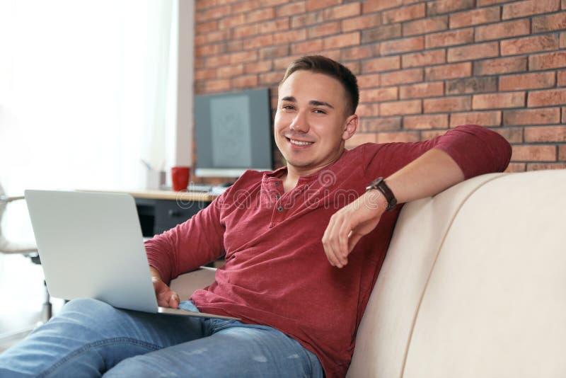 Homem novo que trabalha com portátil fotos de stock