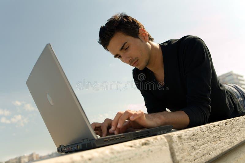 Homem novo que trabalha com portátil foto de stock royalty free