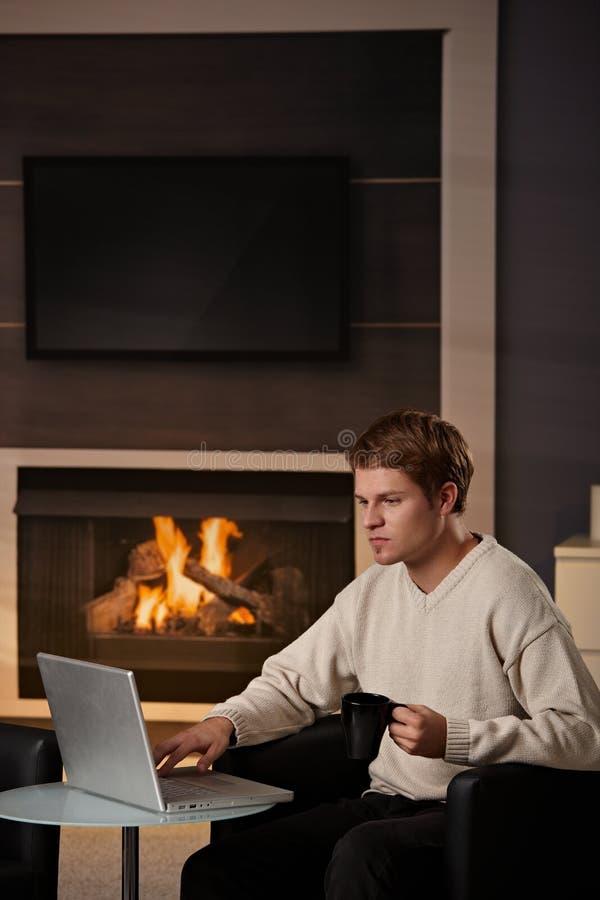Homem novo que trabalha em casa foto de stock royalty free