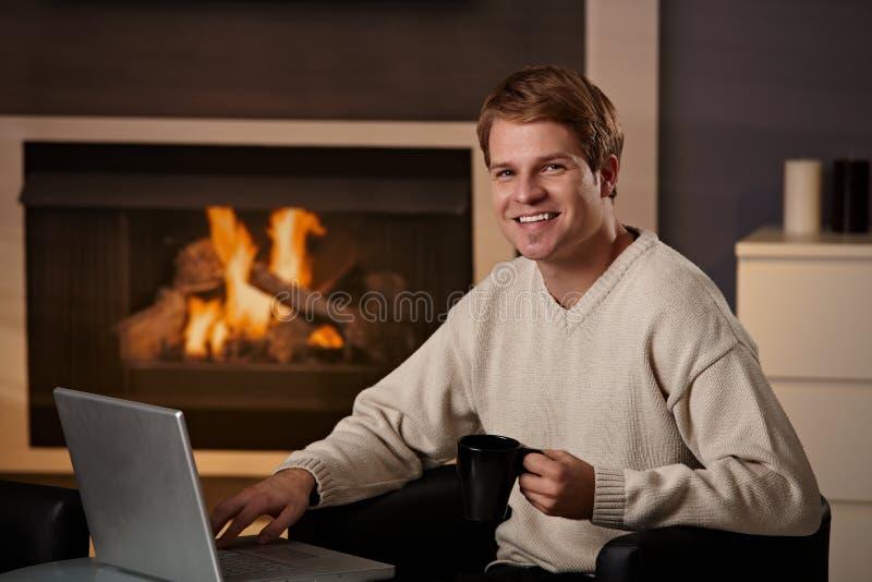 Homem novo que trabalha em casa foto de stock