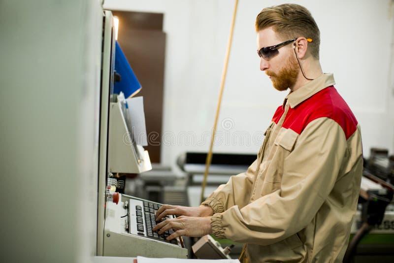 Homem novo que trabalha na f?brica fotografia de stock royalty free