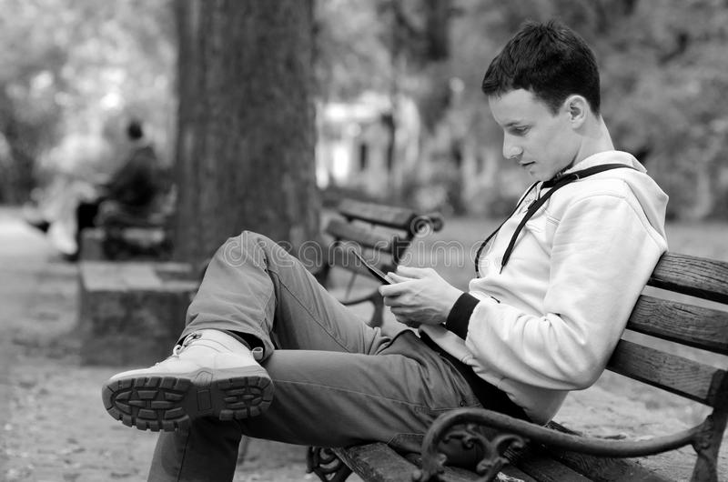 Homem novo que trabalha na tabuleta no parque imagem de stock