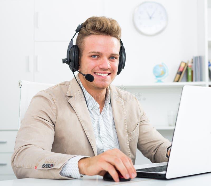 Homem novo que trabalha no centro de chamada foto de stock royalty free
