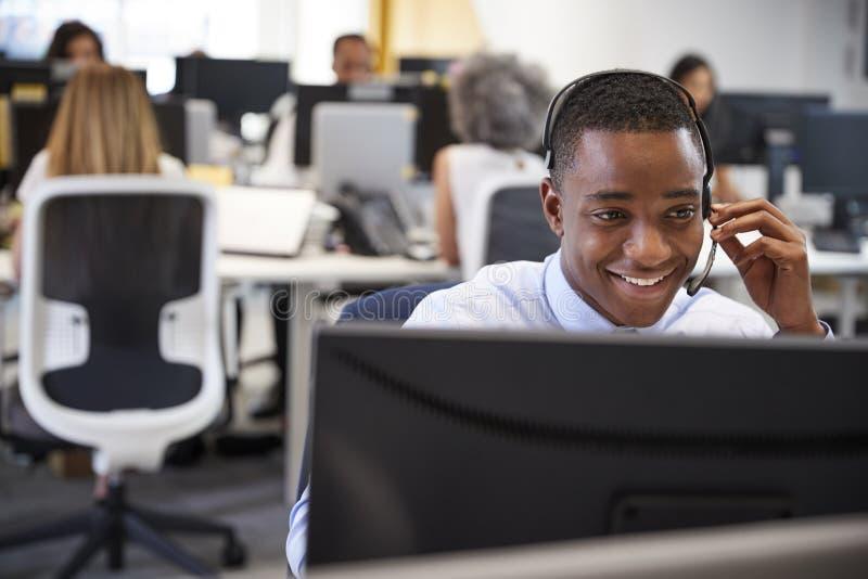 Homem novo que trabalha no computador com os auriculares no escritório ocupado fotografia de stock royalty free