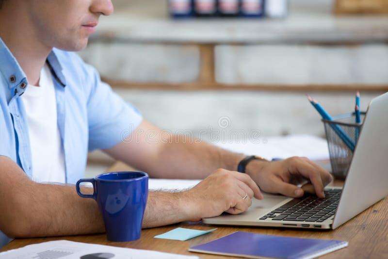 Homem novo que trabalha no escritório foto de stock royalty free