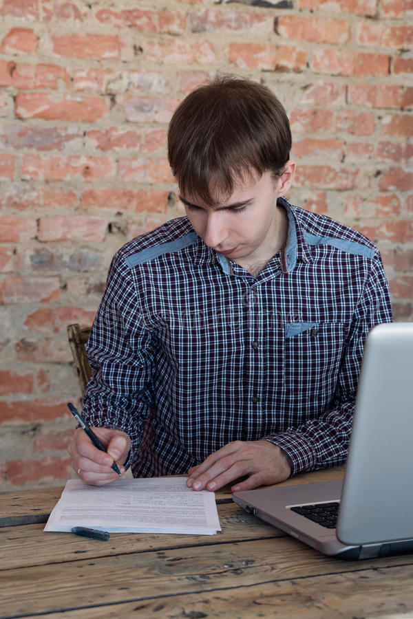 Homem novo que trabalha no escritório, sentando-se na mesa, escrevendo fotografia de stock