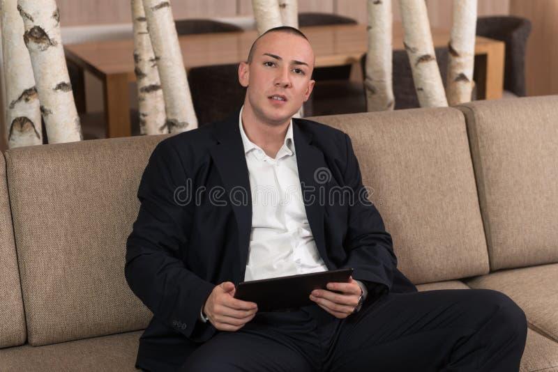 Homem novo que trabalha no portátil do computador em casa imagem de stock royalty free
