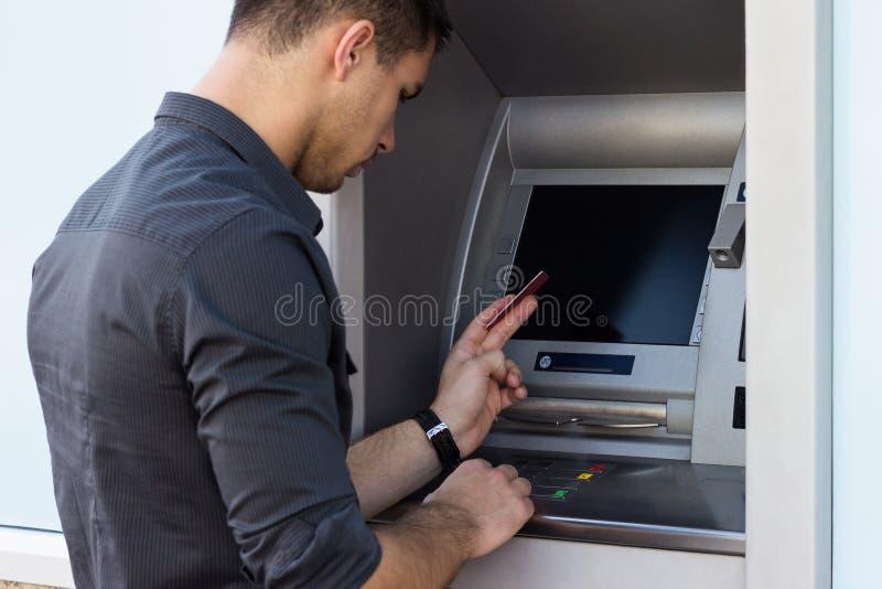 Homem novo que usa o ATM imagens de stock royalty free