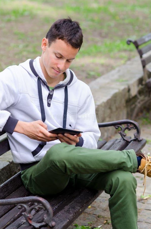 Homem novo que usa o dispositivo móvel no parque fotografia de stock