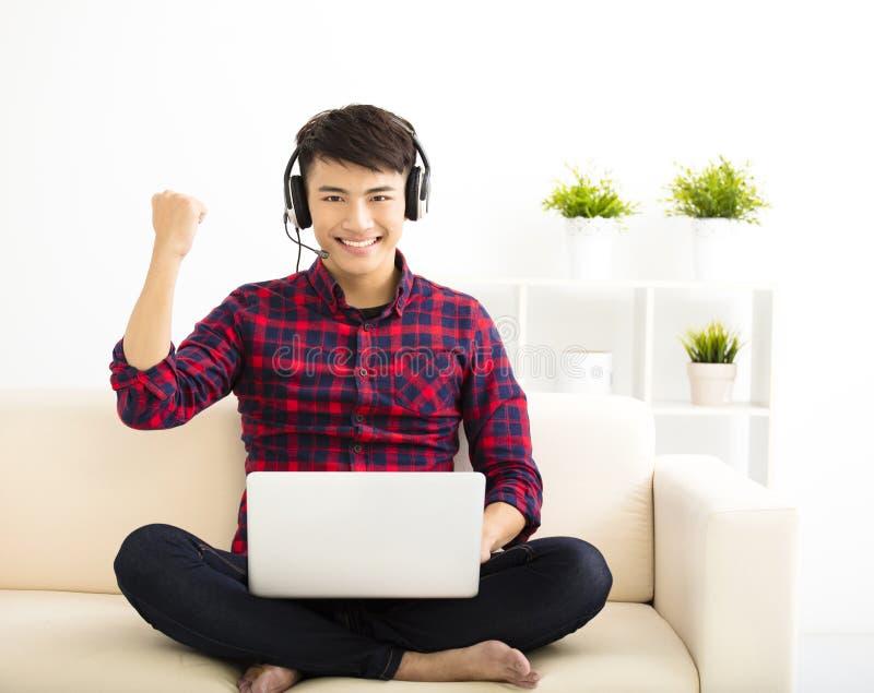 homem novo que usa o laptop com auriculares imagem de stock